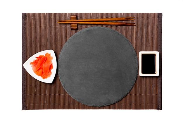 Пустая круглая тарелка из черного сланца с палочками для суши, имбирем и соевым соусом на темной бамбуковой циновке