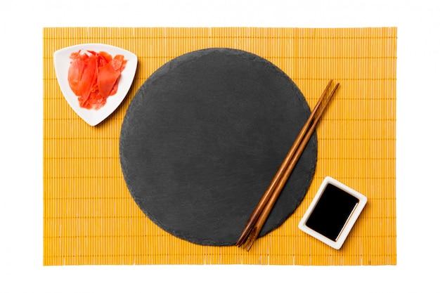 Чёрная сланцевая тарелка с круглыми палочками для суши