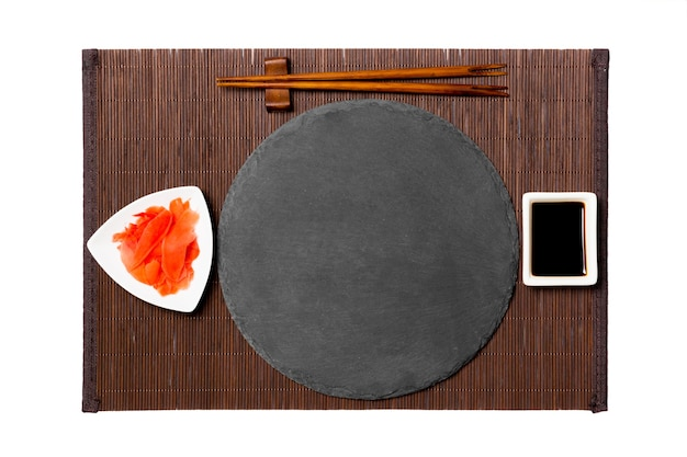 Emptyround black slate plate with chopsticks for sushi, ginger and soy sauce on dark bamboo mat