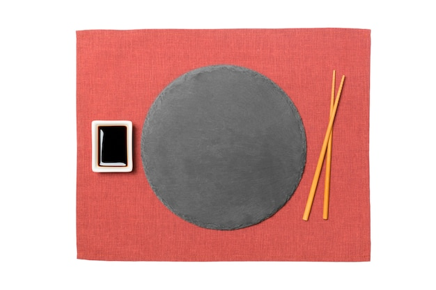 Emptyround black slate plate with chopsticks for sushi and soy sauce on red napkin surface