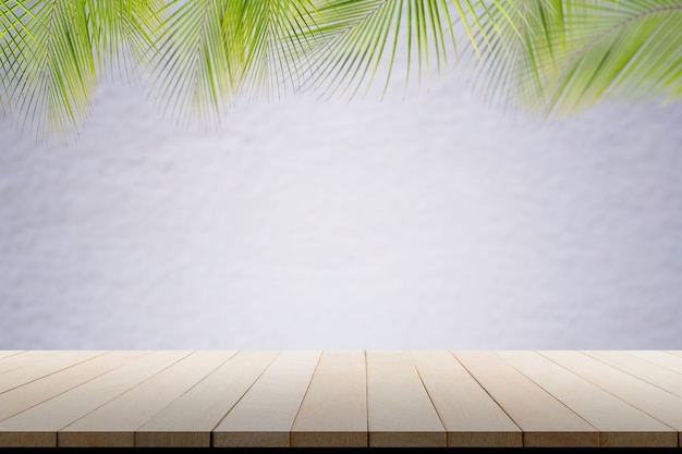 Empy floor wooden perspective with coconut palm leaves wall white pain concrete cement room display room white blank with wooden table background summer tourist travel holidays tropical