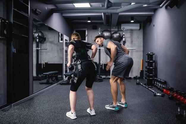 Концепция обучения ems. снимок со спины спортсменки, одетой в костюм ems, и мужчины-тренера в серой спортивной одежде, помогающего ей выполнять упражнения с гантелями и демонстрирующего ей упражнение с гантелями электрическая стимуляция мышц