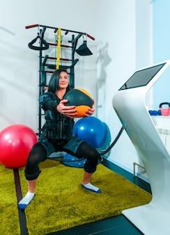 Спортсменка делает упражнения в фитнес-студии ems
