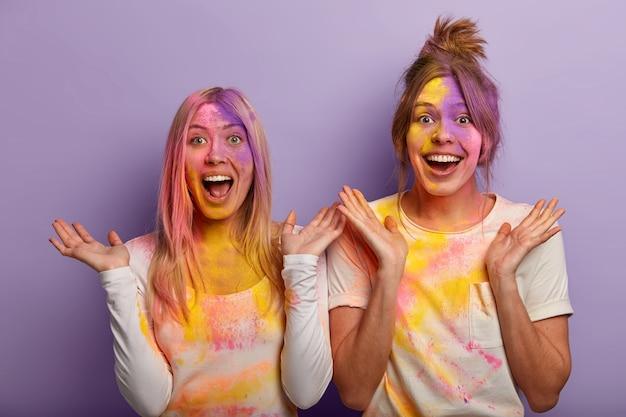 Emtional felici migliori amiche usano la tintura colorata durante il festival di holi, spalmate di polvere arcobaleno colorato, allargano le palme dalla felicità e dal divertimento, celebrano le vacanze di primavera indiana, si inzuppano a vicenda