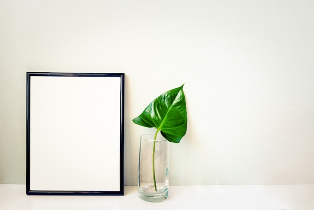 Emty灰色の壁に配置されたクリスタルの花瓶に黒のフォトフレームと緑の植物。