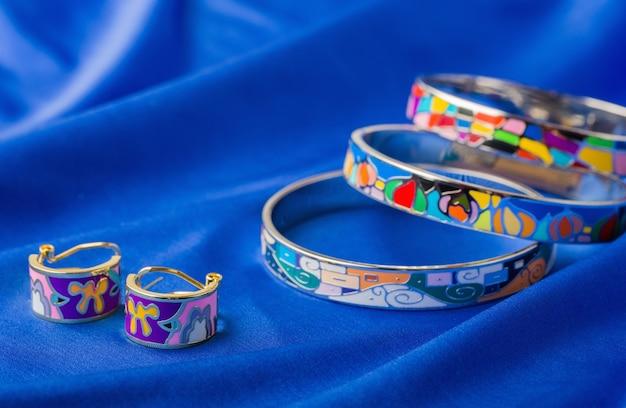 Эмалированные серьги и браслет на синей ткани.