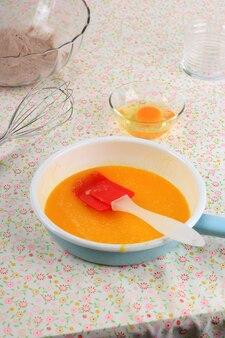 Эмалированная сковорода с топленым маслом, яйцом и шоколадной мукой. приготовление выпечки на кухонном столе
