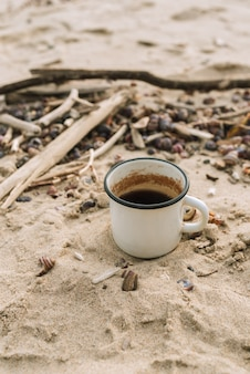 Enamel mug with hot drink standing in a sand on a wild beach, selective focus