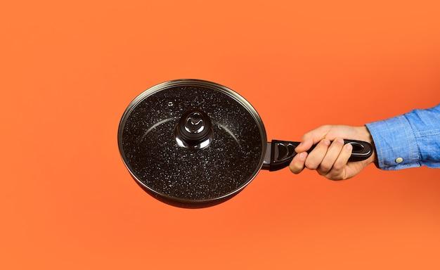 Емкости для приготовления пищи чугунные эмалированные. стеклянная крышка кастрюли. антипригарное покрытие из политетрафторэтилен-тефлона. человек держит новую сковороду. магазин купить товары для кухни. посуда для покупок. посуда.