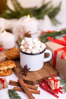 マシュマロとクッキーを添えたホットココアまたはコーヒーのエナメルカップ。木の枝、贈り物、燃えるろうそくの周り。クリスマスムード。はがきや冬の背景。