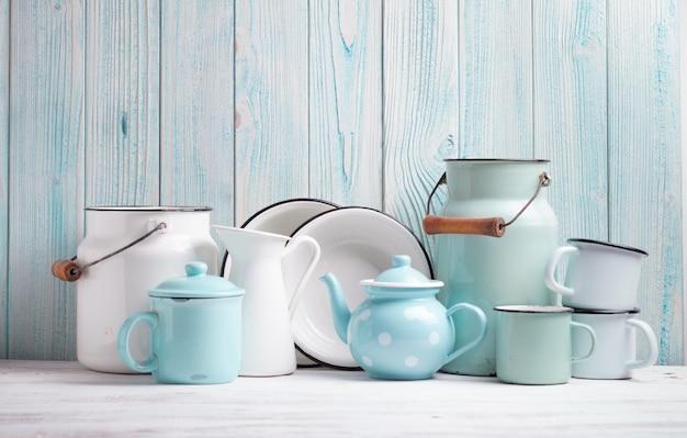 青い木製の壁の上の台所のテーブルのエナメル製品
