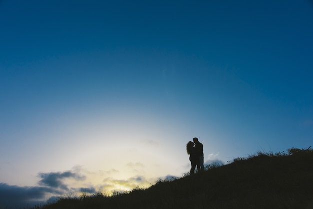Enamored couple embraced at sunset in a backlit photo