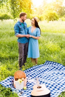 Enamored couple hugging standing by checkered plaid on picnic