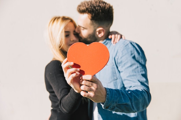 Enamored couple posing with red heart