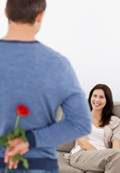 Enamored man hiding a flower behind his back for his girlfriend