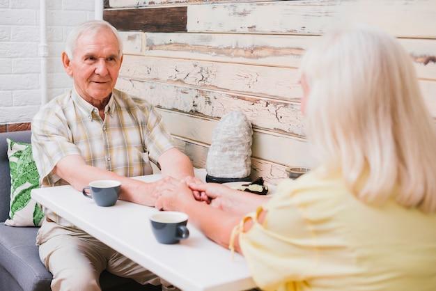カフェに座っている夢中の年配のカップル