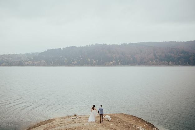 매혹 된 웨딩 커플은 흰색 강아지와 함께 호수 근처 산책.