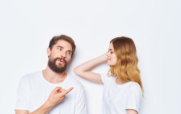 매혹 된 여자와 남자 티셔츠 가족 친구는 그들의 손으로 몸짓 재미.
