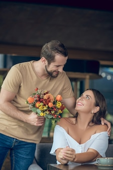 Влюбленный молодой бородатый мужчина с цветами стоит возле счастливой женщины в кафе