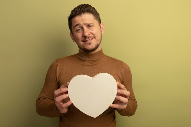 Innamorato giovane biondo bell'uomo che tiene a forma di cuore che sembra isolato sulla parete verde oliva con spazio di copia