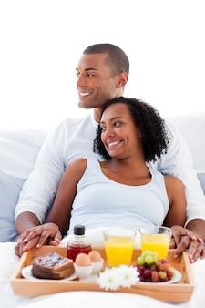 ベッドで横たわっている朝食を持つ恋人カップル