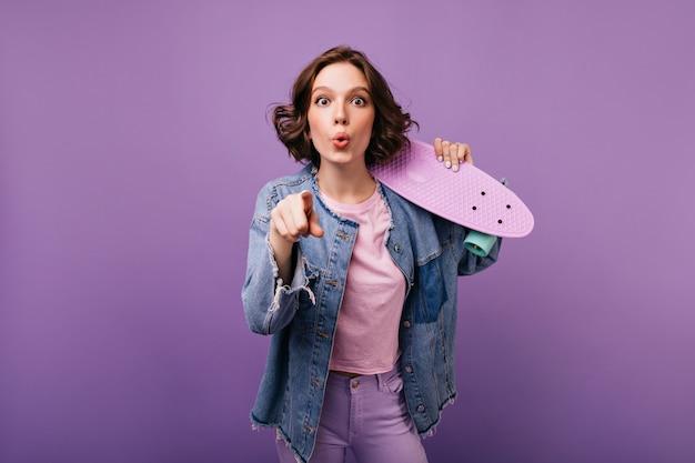 Очаровательная активная девушка в джинсовой куртке, выражающая удивленные эмоции. крытое фото довольно курчавой женщины брюнет с скейтбордом.