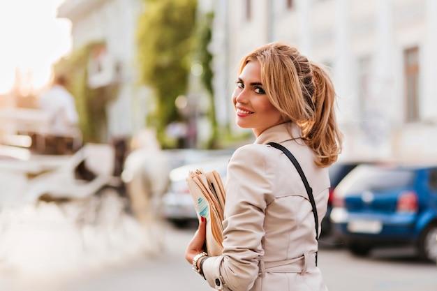 Incantevole ragazza bionda in giacca beige alla moda divertendosi fuori a piedi in auto