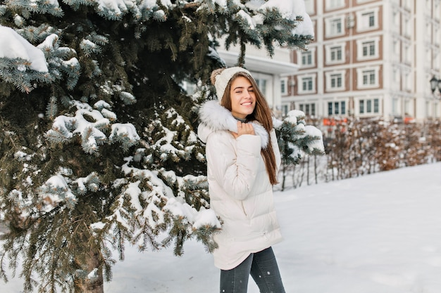 Enchanting blonde woman in white jacket and black jeans posing during walk in winter park. outdoor photo of pretty fashionable woman having fun in december morning..