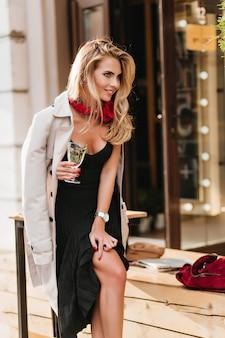 日焼けした肌で魅惑的な金髪の女性、グラスワインを持って笑っている。シャンパンを楽しんでいる黒のドレスとベージュのコートで興奮した金髪の女性の屋外の肖像画。