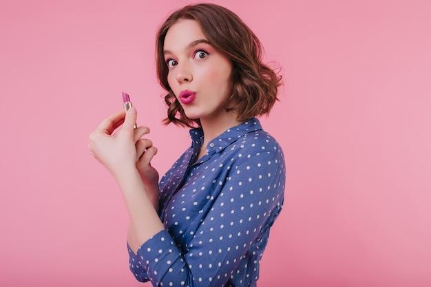 化粧をしている間、巻き毛の短い髪が浮気している魅惑的な茶色の目の女の子。ピンクの壁に口紅でポーズをとってブラウスの陽気な女性モデルの屋内の肖像画。