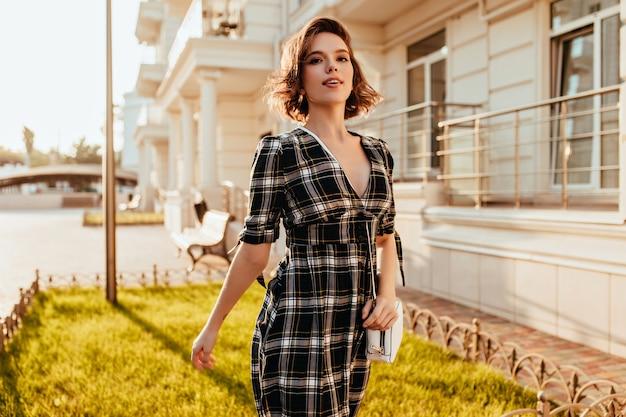 街でポーズをとるエレガントなドレスを着た魅惑的な白人女性。晴れた日に通りを歩いているウェーブのかかった髪の嬉しい白人女性。