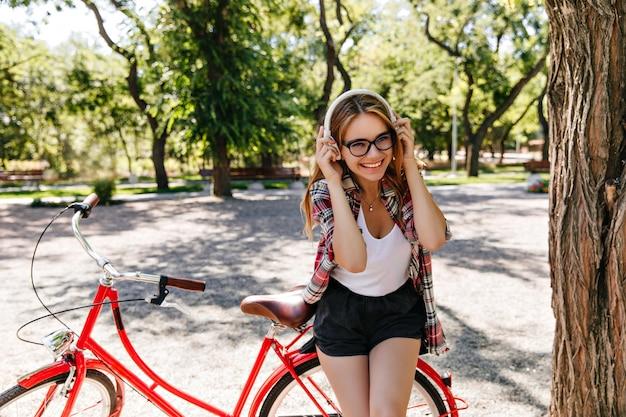 公園で身も凍るようなメガネとヘッドフォンで魅惑的な白人モデル。自転車の前で笑っているブロンドの髪を持つ壮大な若い女性の屋外写真。