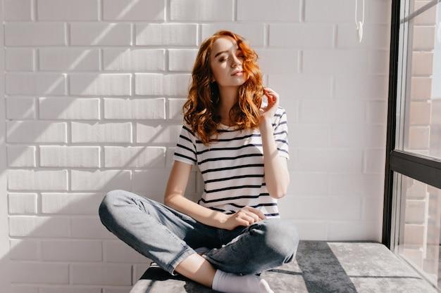 窓枠に座っている魅惑的な巻き毛の女性モデル。目を閉じてポーズをとるストライプのtシャツを着た熱狂的な白人の女の子。