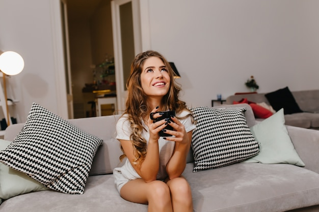 Очаровательная европейская женщина пьет чай на диване и смотрит вверх с улыбкой