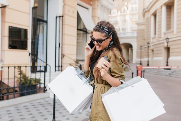 Incantevole donna fashionista parla al telefono e sorridente nel weekend autunnale