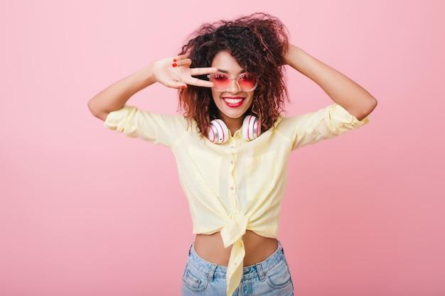 余暇とダンスを楽しむ夏服の魅惑的な女性モデル。黒髪で遊んでピースサインでポーズをとる素晴らしいアフリカの女性の屋内の肖像画。