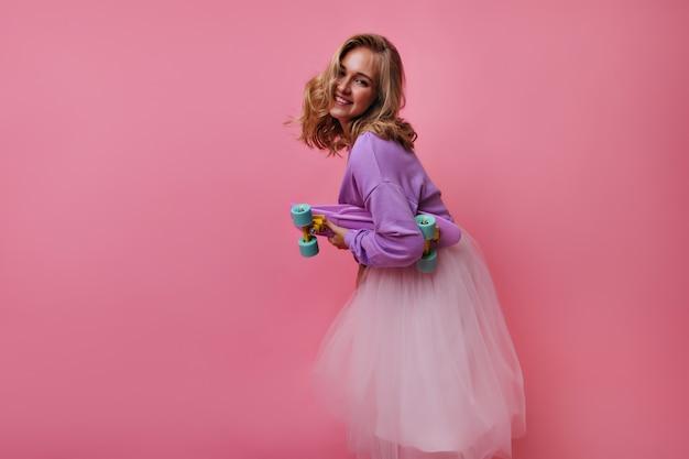 Incantevole modello femminile in gonna lussureggiante e camicia viola in posa con lo skateboard. ritratto dell'interno della ragazza bionda interessata scherzosamente