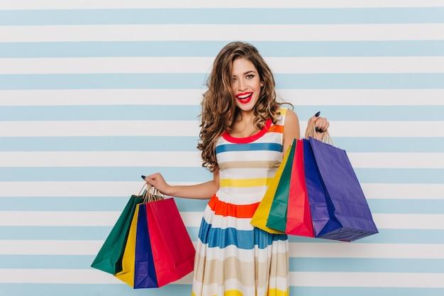 Очаровательная женщина-шопоголик демонстрирует новые покупки. фото в помещении смеющейся экстатической женщины с темными волосами.