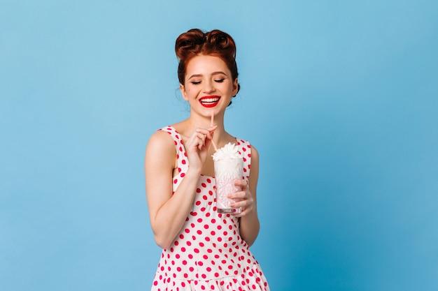 ミルクセーキを飲む魅惑的な生姜の女の子。青いスペースで飲み物を楽しんでいる水玉模様のドレスを着た幸せな女性のスタジオショット。