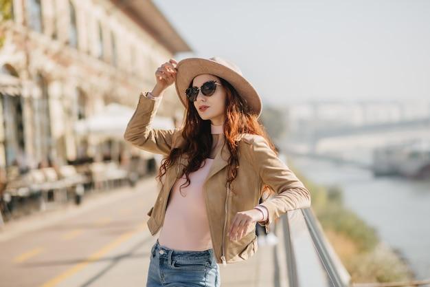 Incantevole donna allo zenzero che tocca il suo cappello mentre posa sulla parete del mare