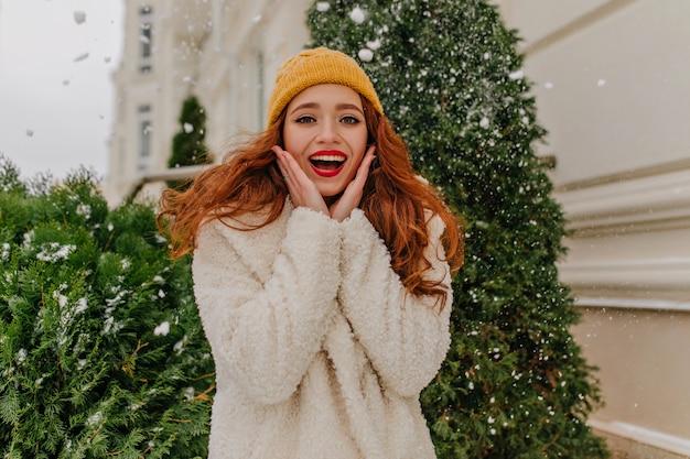 冬にポーズをとる魅惑的な生姜の若い女性。笑顔でトウヒの近くに立っているかなり白人の女の子。