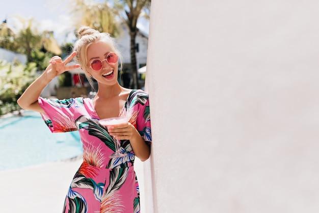 핑크 드레스의 매혹적인 소녀는 피서지에서 즐거운 시간을 보냅니다.