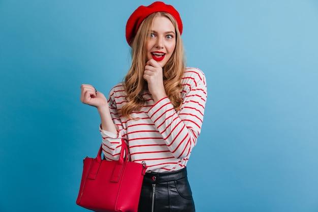 赤いベレー帽の魅惑的な女の子。青い壁に分離されたフランスのブロンドの女性の正面図。