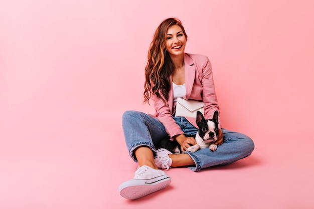 강아지와 함께 포즈를 취하는 흰색 스포츠 신발에 매혹적인 소녀. 귀여운 불독 강아지와 함께 바닥에 앉아 매력적인 여자를 웃고.