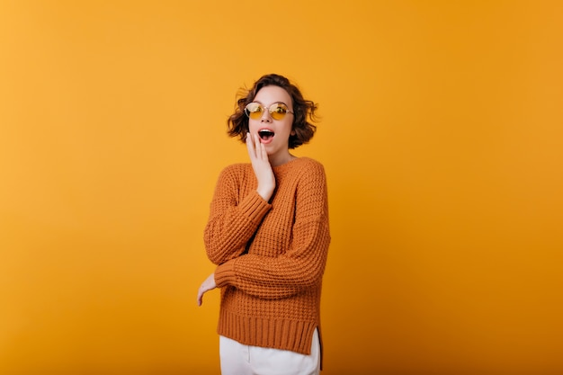 Enchanting girl in stylish knitted attire expressing amazement. indoor photo of romantic caucasian woman with short wavy hair.
