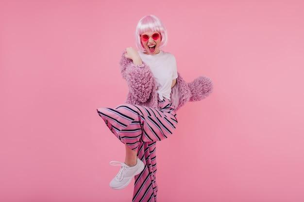 Incantevole ragazza in eleganti scarpe da ginnastica bianche che esprimono emozioni positive durante la danza. signora che ride con i capelli rosa in posa in giacca di pelliccia