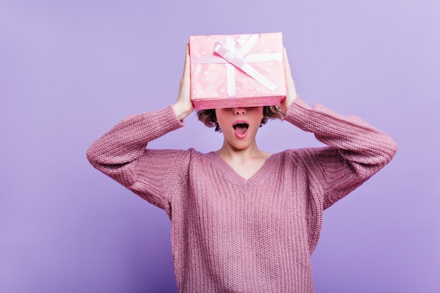 Enchanting girl wears woolen sweater isolated on purple wall with pink present box. indoor photo of happy short-haired woman having fun  with new year gift.