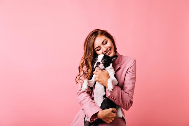 눈으로 프랑스 불독을 껴 안은 긴 헤어 스타일로 매혹적인 소녀가 닫힙니다. 귀여운 강아지를 들고 웃고 평온한 생강 여성 모델의 실내 초상화.