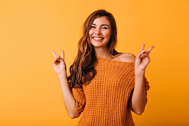 Incantevole ragazza con l'acconciatura lunga in posa con il segno di pace sull'arancio. felice modello femminile in maglione lavorato a maglia alla moda che ride in studio.