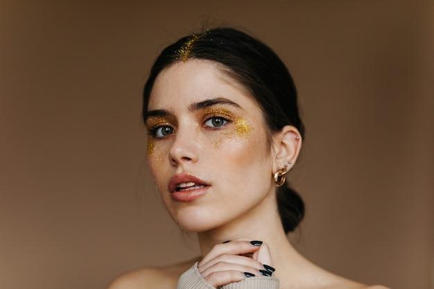 Очаровательная девушка со стильным золотым макияжем. крытый крупный план восторженной дамы с черными волосами.
